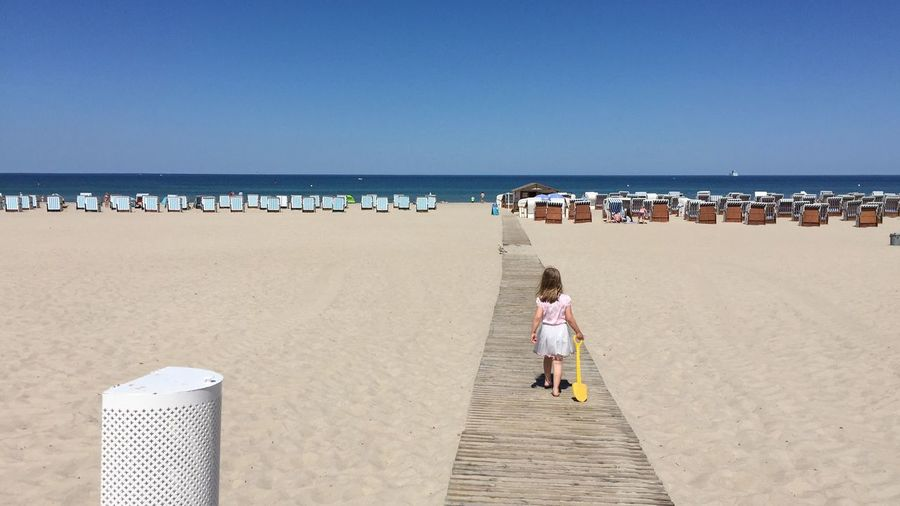 Rear View Of Girl Walking On Boardwalk At Sandy Beach