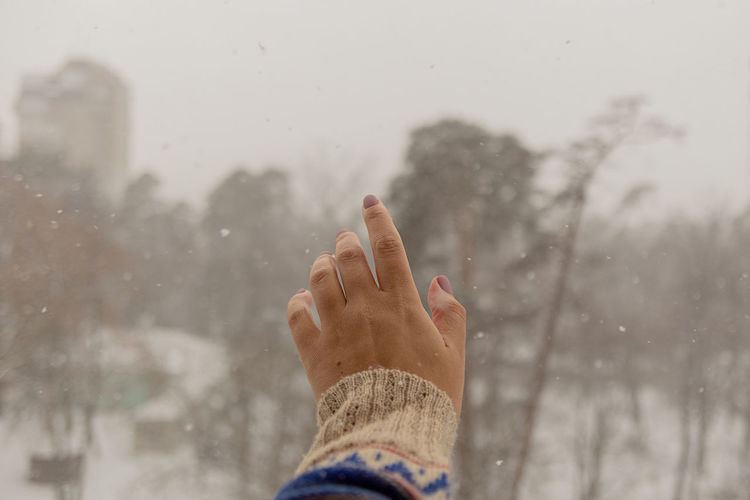 Woman's hand reaches for snowflakes during snowfall with views of nature and houses