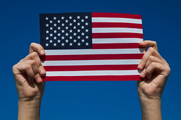 Close-Up Of Hands Holding American Flag Against Clear Blue Sky