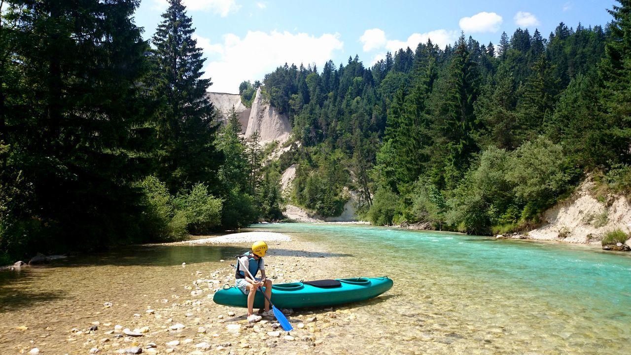 Man sitting on canoe at isar riverbank
