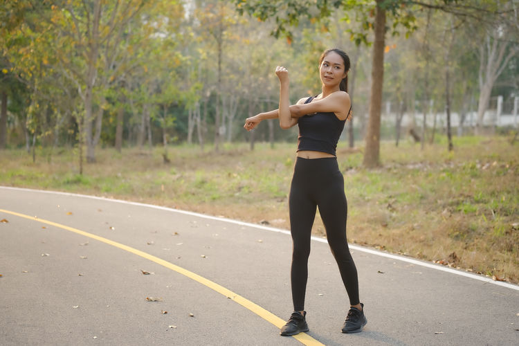 Full length of young woman standing on road