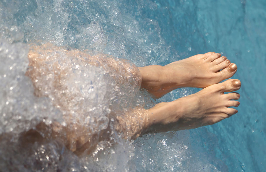 two feet of a young woman during the hydromassage session in the spa pool Foot Gold Relaxing Resort Hotel Therapy Wellness Woman Barefeet barefoot Feet Human Body Part Hydromassage Leisure Activity Massage Massage Therapy Massaging One Person Realx Relax Relaxing Moments Resort Resorts Spa Spa Treatment Water