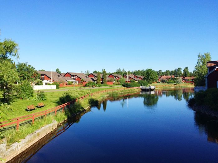 River and houses against clear sky