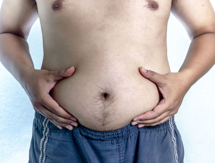 Midsection of shirtless man holding belly while standing against white background