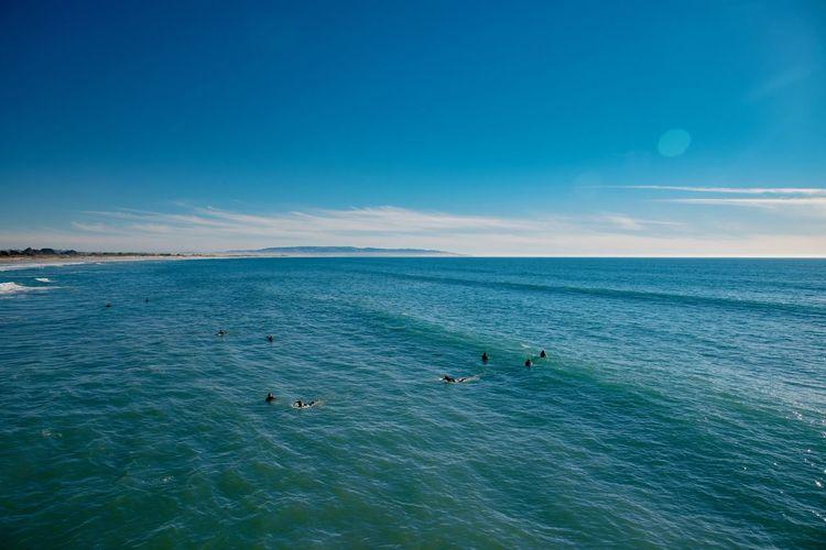 People swimming in sea against blue sky