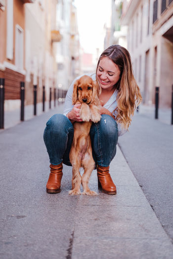 Smiling woman playing with dog in city