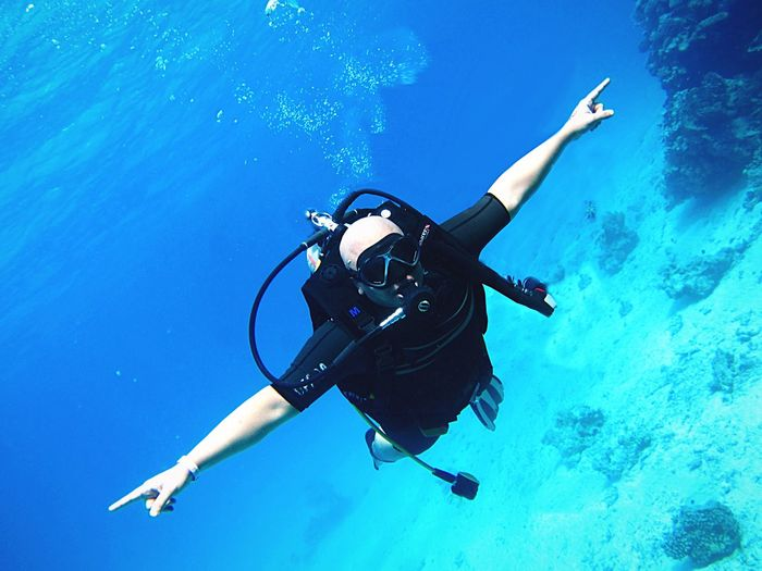 Man With Arms Outstretched Scuba Diving In Sea