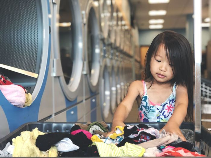 Girl with laundry in laundromat