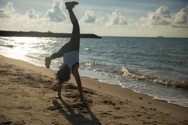 Athlete girl somersault on beach at sunrise Arms Raised Beach Beauty In Nature Exercising Full Length Handstand  Healthy Lifestyle Horizon Horizon Over Water Land Leisure Activity Lifestyles Nature One Person Outdoors Real People Sand Scenics - Nature Sea Sky Somersault  Sport Water