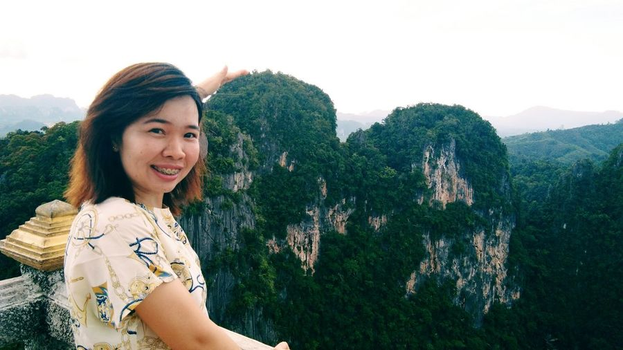 Portrait of woman smiling while gesturing against mountains