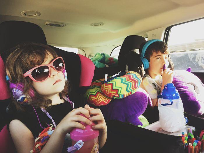 Portrait of siblings sitting in car