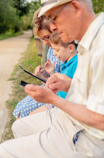 Closeup of grandchild teaching to his grandmother to use a electronic tablet on a park bench. Focus on grandmother. Generation values concept. Female Woman Three Caucasian Parent Real Communication TAB Touchscreen Reading Together Education Internet Sitting Male Adult Background Man Kid Child People Happy Boy Touchpad Technology Pad Leisure Lifestyle Elderly Smartphone Smart Phone Outdoors Bench Park Nature Family Generation Using Learn Teach Closeup Electronic Tablet Senior Grandmother Grandfather Grandparent Grandchild Grandson