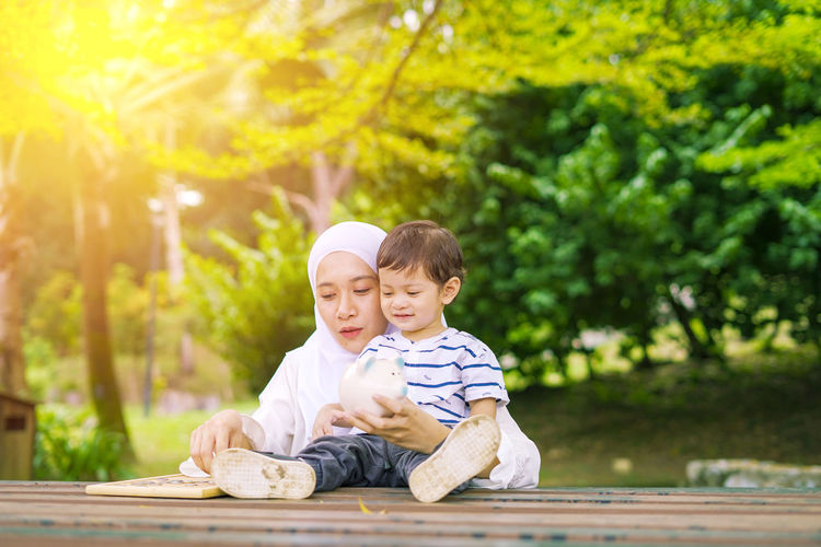 Young woman with her cute son learn how to put coins into piggy bank. Future planning concept. Child Childhood Togetherness Family Males  Men Bonding Son Innocence Boys Sitting Tree Parent Casual Clothing Offspring Family With One Child Emotion Day Plant Positive Emotion Outdoors