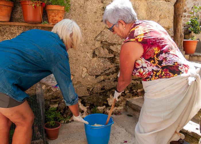 Two women recycling soap outdoors