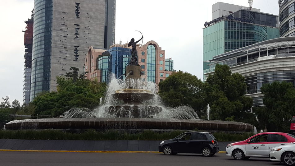 Architecture Building Exterior Built Structure Car City Day Fountain Land Vehicle Mode Of Transport Motion No People Outdoors Sky Skyscraper Spraying Transportation Tree Water