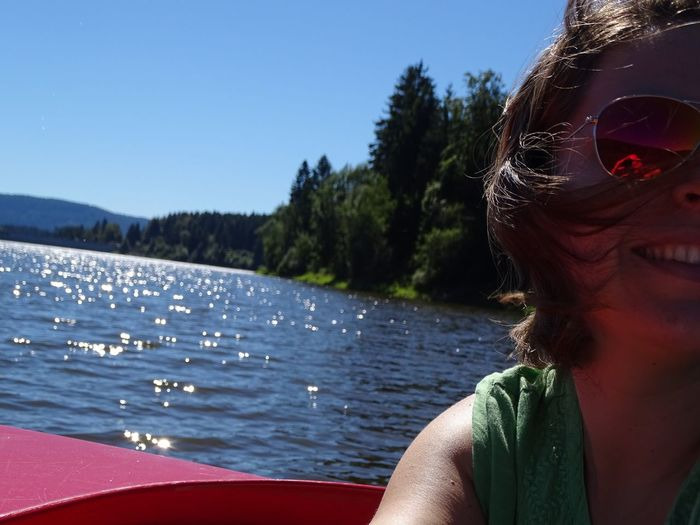 Close-Up Of Happy Woman On Boat In River Against Sky During Sunny Day