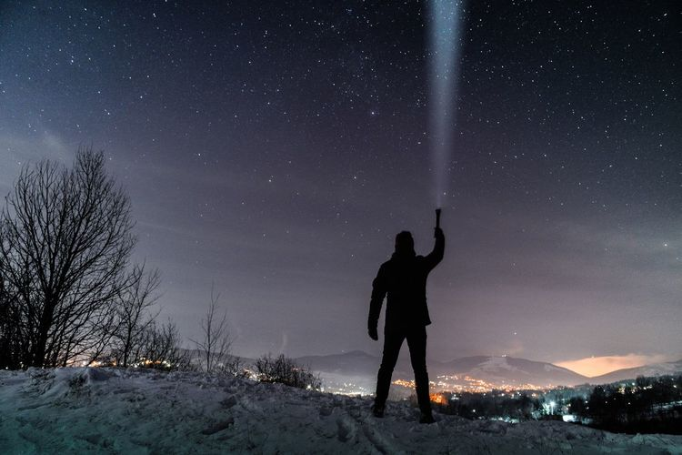 Full length of silhouette man holding illuminated flashlight while standing against star field at night