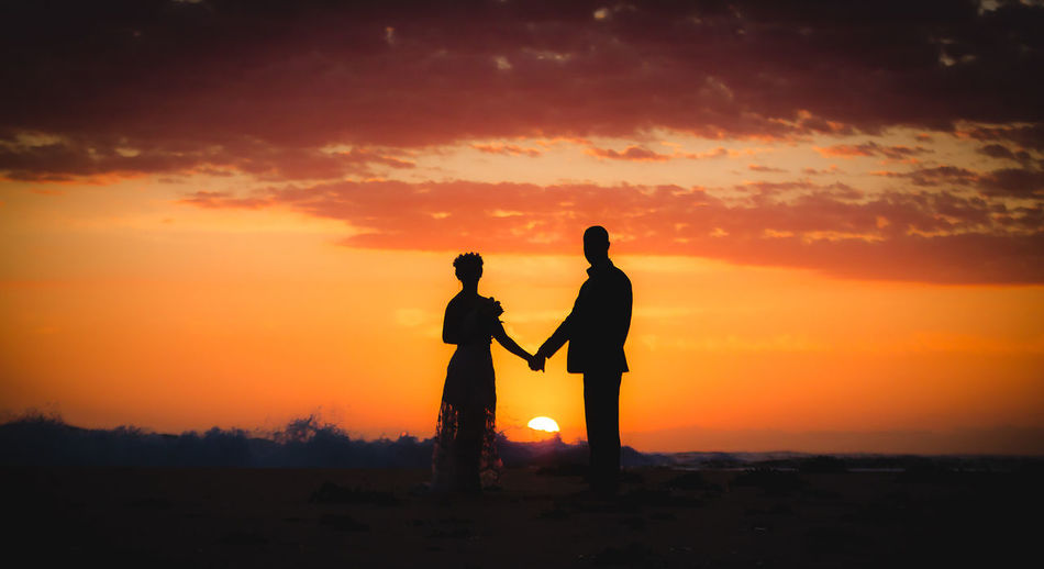 Silhouette Couple Standing On Field Against Sky During Sunset