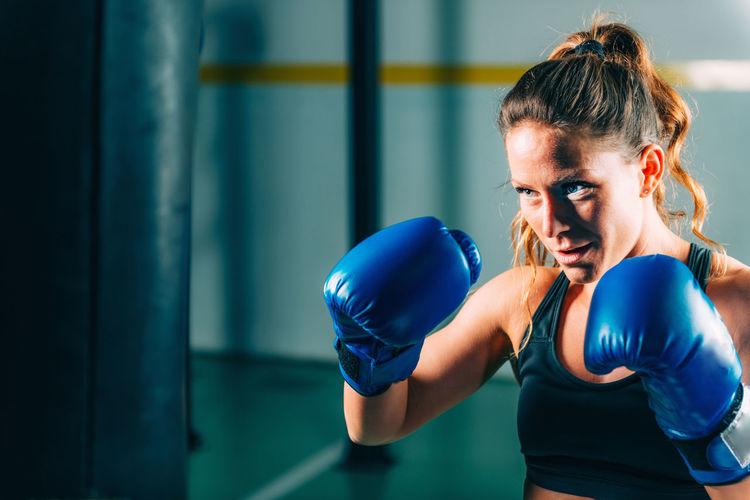 Boxer hitting on punching bag at gym
