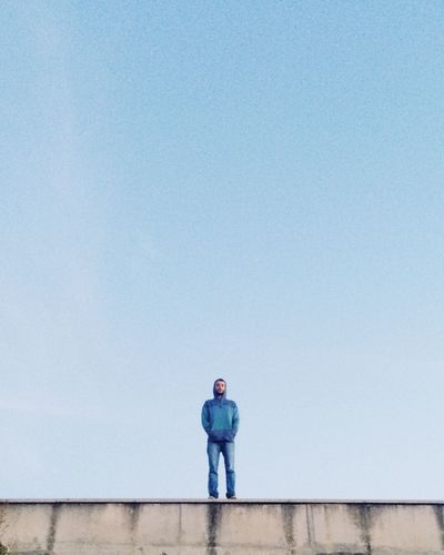 Low angle view of man standing on surrounding wall against sky