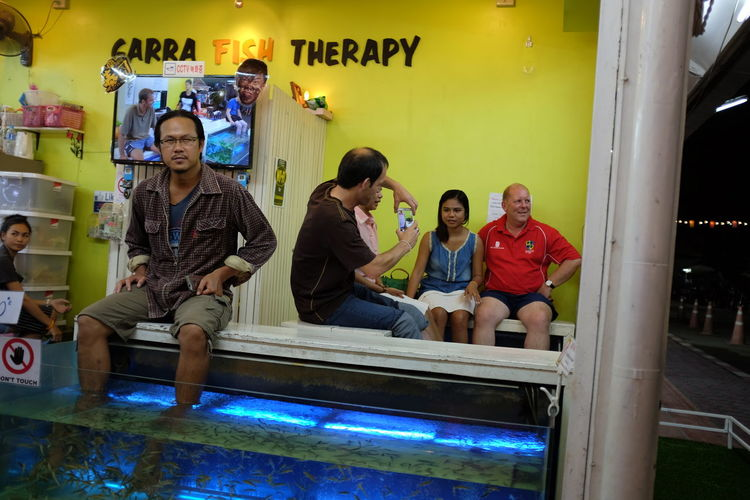 fish therapy ASIA Asian  Everybodystreet Fish Tank Fish Therapy Leisure Activity Lifestyles Market Scene Night Market People Having Fun People Taking Photos People Taking Pictures Street Photography Streetphotography Travel Photography Yellow Wall