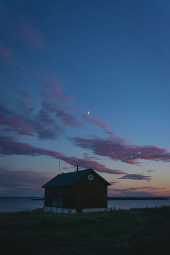 House by sea against sky during sunset