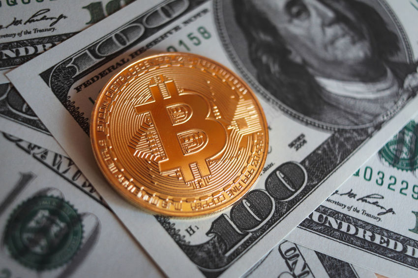 Bitcoin cryptocurrency token on a pile of US $100 dollar bills Bitcoin Cryptocurrency Blockchain Blockchain Technology Encrypted Wallet Secure Cyber Money Around The World Money Currency Dollar Business Cash Coin Finance Bank Wealth Bill Banking Bills Financial Investing Investment Savings