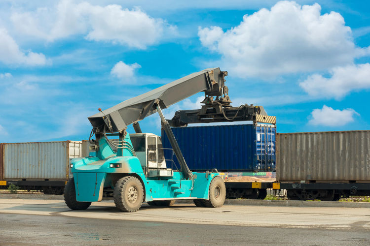 Forklift containers Logistics Shipping Containers Blue Cargo Container Cloud - Sky Commercial Dock Commercial Land Vehicle Day Equipment Export Factory Freight Transportation Import Industry Land Vehicle Mode Of Transport Outdoors Port Shipping  Shipping Docks Shipping Terminal Sky Sunlight Train Transportation