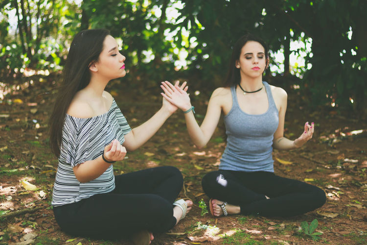 Friends meditating while sitting at park