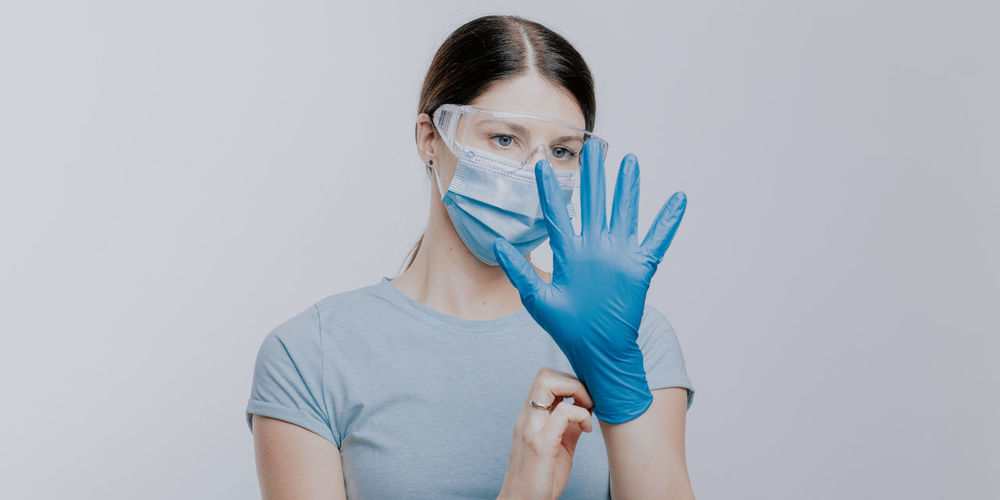 Doctor in mask wearing surgical glove against gray background
