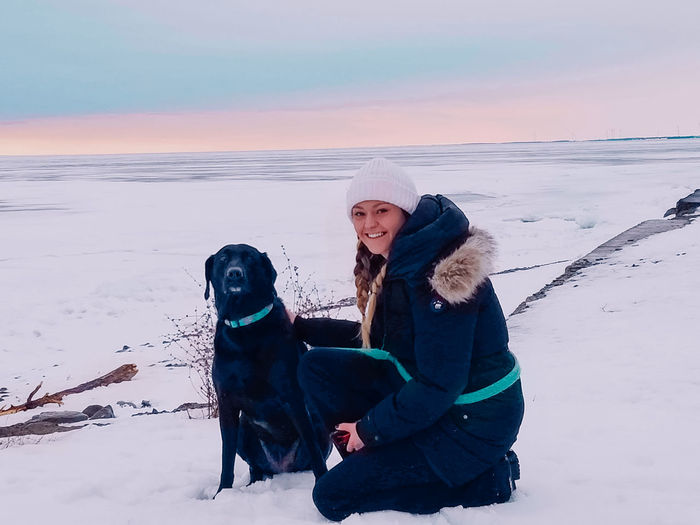 Woman with dog sitting on snow land