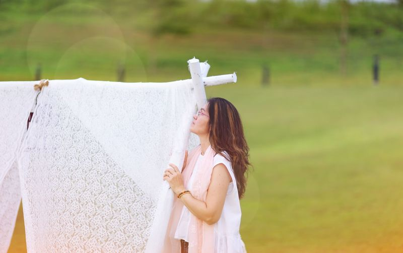 Side view of woman standing by laundry on clothesline