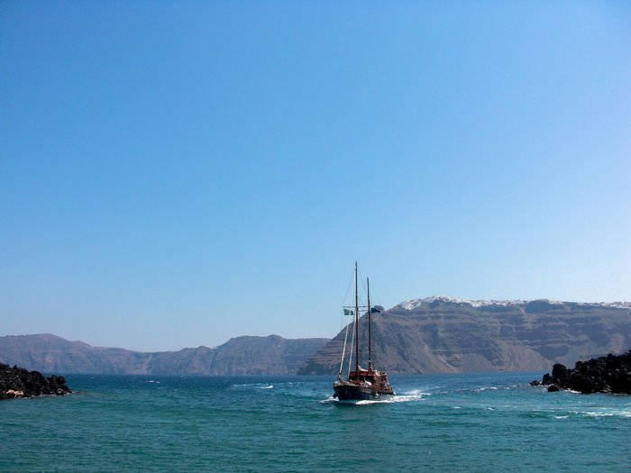 High Angle View Of Boat Moving On River At Santorini Against Clear Blue Sky