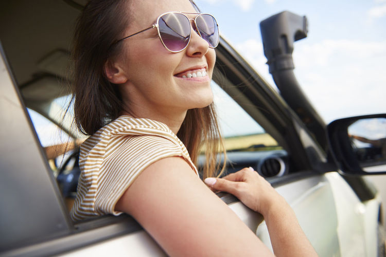 Smiling young woman looking at view during road trip Car Passenger Woman Travel Road Trip Vacation Summer Journey Adventure Look At View Look Window Trip Transportation Travel Destinations Young Woman Adult People Indoors  City City Life Taxi Service Beautiful Woman One Woman Only Only Women Carefree Freedom Sunglasses Tourist Tourism Real People Fun Drive Van Females Happiness Joy Smiling Toothy Smile Glasses