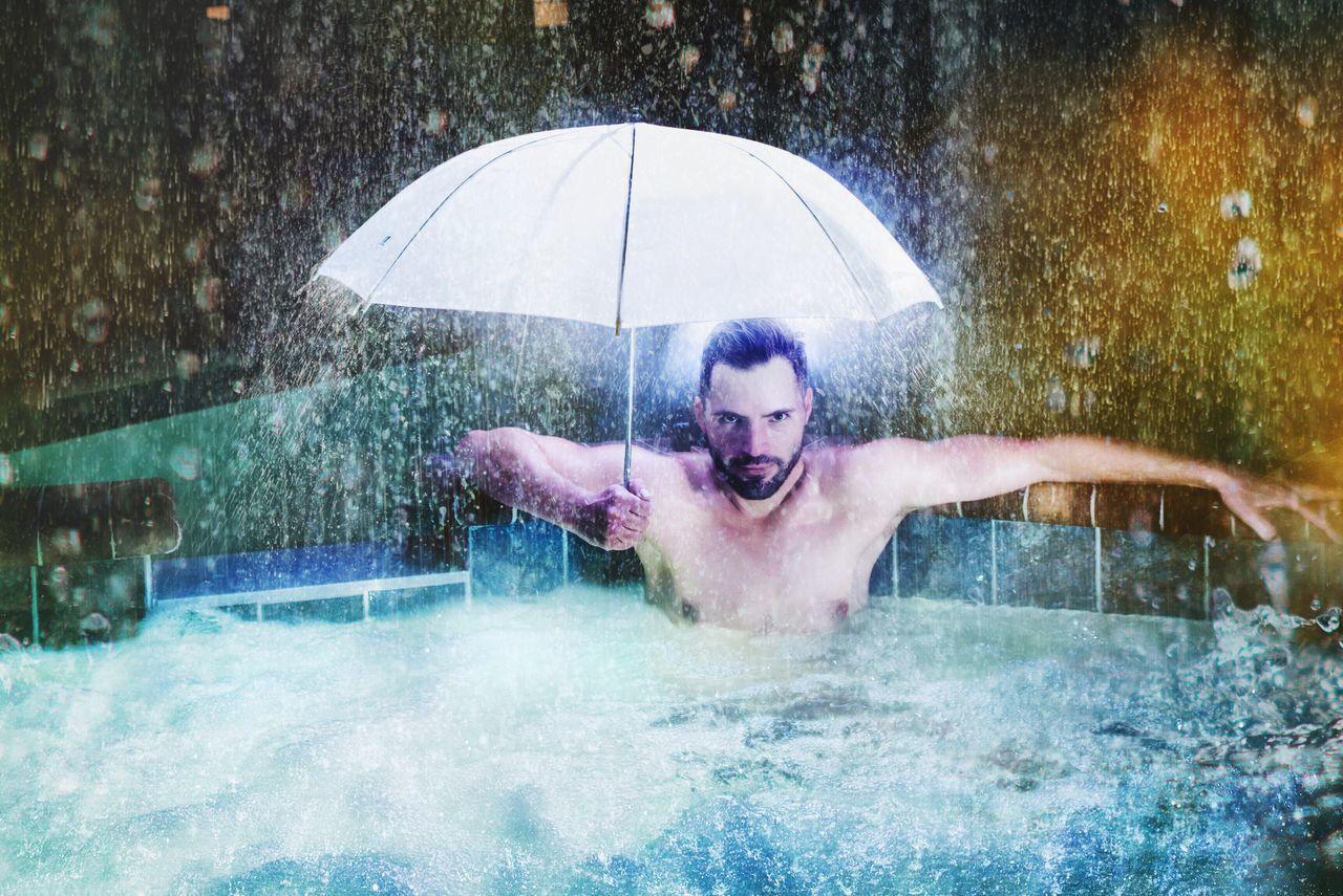 Man Holding Umbrella In Swimming Pool In The Rain