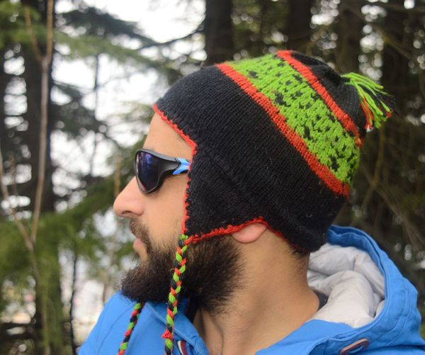 Side view of handsome bearded man wearing knit hat during winter