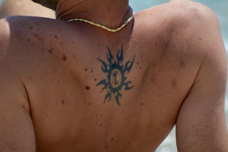 Midsection of shirtless man back with tattoo