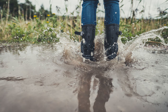 Legs of a young woman with rubber boots dancing and jumping in a puddle Splashing Splash Water Dance Joy Only Women Girl Woman People Puddle Human Legs Legs Rubber Boots Jumping Dancing