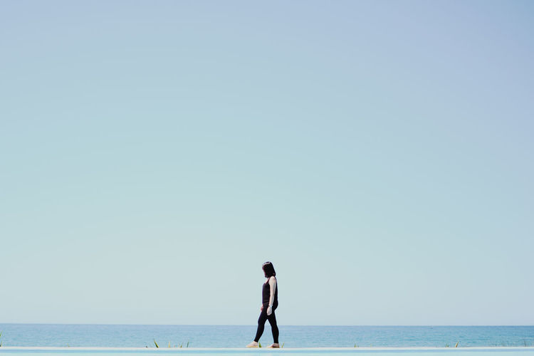 Side View Of Woman Walking By Sea