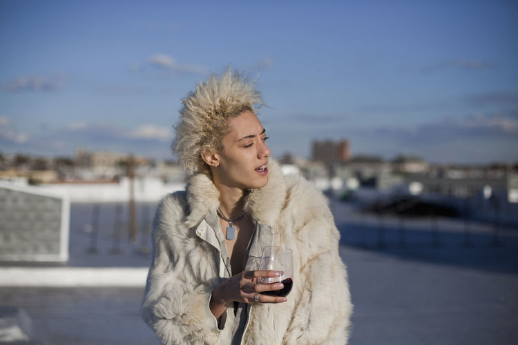 Young woman drinking while standing in winter