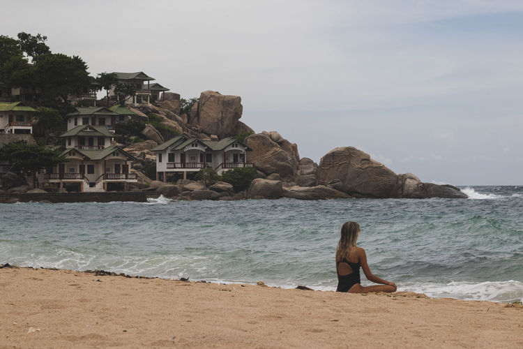 Full length of man on rock at beach against sky