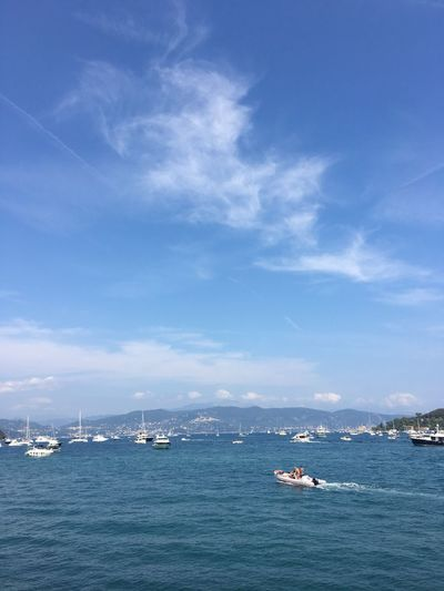 Boats sailing in sea against blue sky