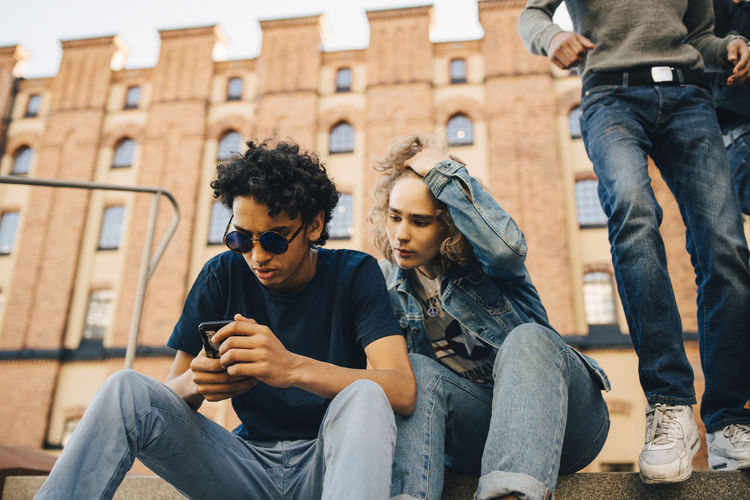 Friends sitting on mobile phone outdoors