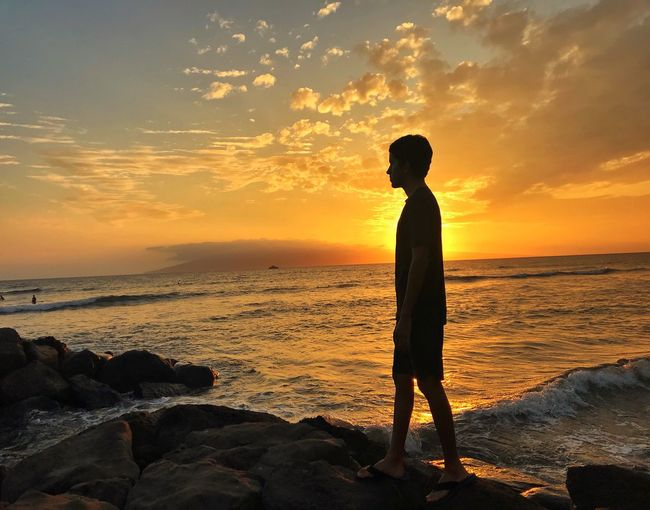 Silhouette teenage boy standing on rock at beach against sky during sunset