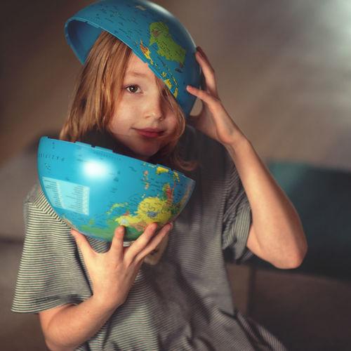 Portrait of happy girl holding globe