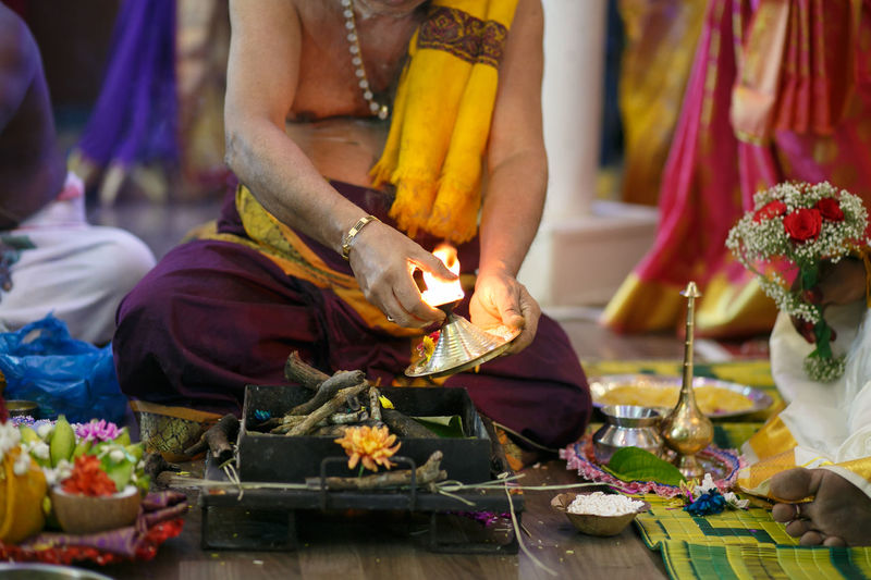 Low section of sadhu holding oil lamp during wedding ceremony