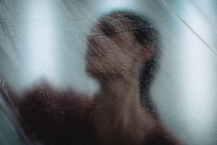 Close-up portrait of woman with reflection on glass