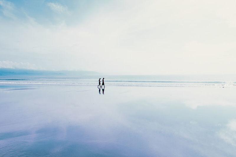 People Walking At Beach Against Sky