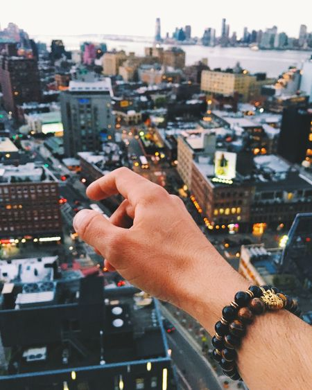 Hand Pointing Towards Cityscape