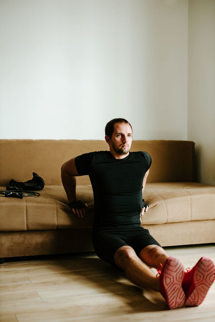 Portrait of man sitting on floor at home